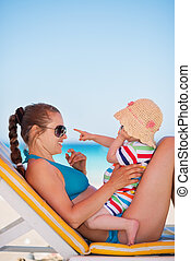 Mother with baby on beach playing with sunglasses