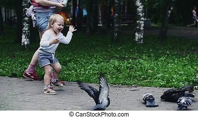 Mother with baby on hands and son feeding doves in park. Boy run, birds fly away