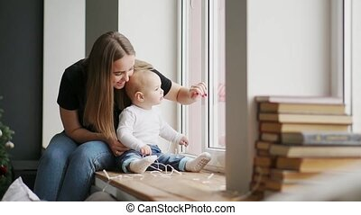 Mother with baby sitting at the window and play