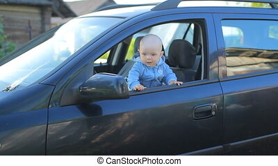 Mother with baby sitting in the car on the driver's seat. Kid play smiling