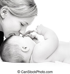 Mother with baby - Happy mother kissing baby girl against...
