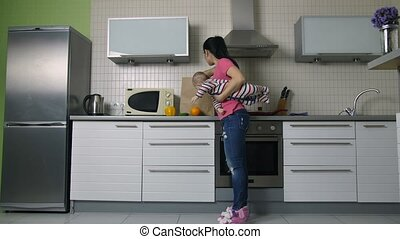 Mother with baby unloading shopping bag in kitchen