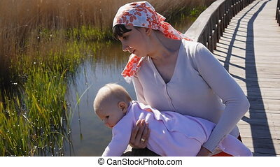Mother with baby watching bog in national park. Young mom...