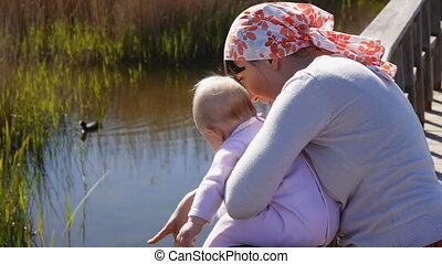 Mother with baby watching fauna of bog in national park