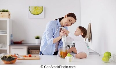 mother with blender cooking baby food at home