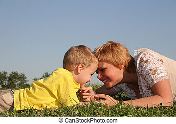 mother with boy lies on meadow
