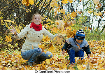 mother with   boy throw up maple leaves