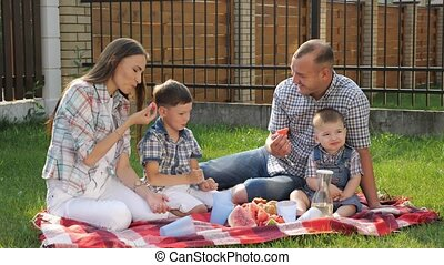 mother with brown hair sits with handsome father and boys -...