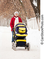 mother with carriage in winter park