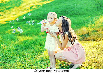 Mother with child blowing soap bubbles together on grass in summer day