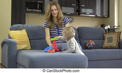 mother with child daughter play with colorful education circles pyramid on sofa