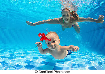 Mother with child dive underwater in swimming pool