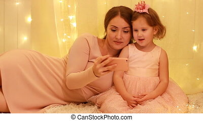 Mother with child girl looking on the mobile phone screen and playing downloaded application.
