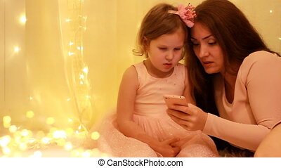 Mother with child girl looking on the mobile phone screen...