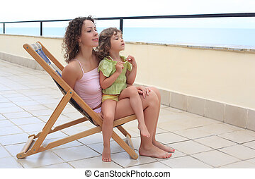 mother with child in lounge on veranda