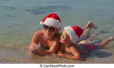 Mother with child in Santa hat enjoying family Christmas tropical beach vacation
