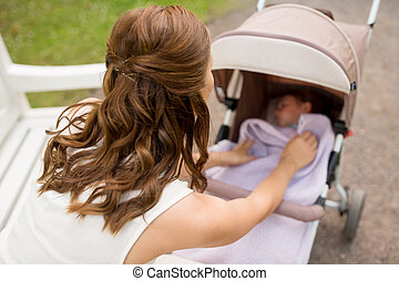 mother with child in stroller at summer park