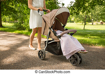mother with child in stroller walking at park