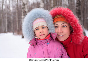 Mother with child in wood in winter