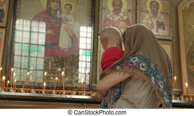 Mother with child lighting prayer candle in Christian Orthodox Church