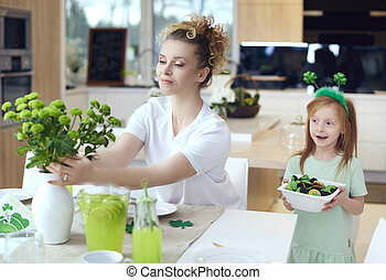 Mother with child make preparations for Saint Patrick's Day