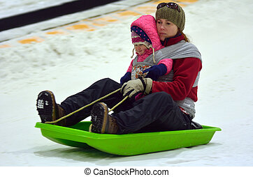 Mother with child on a snow slid slide downhill
