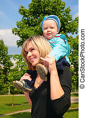 Mother with child on shoulders outdoor