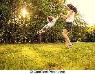 Mother with child playing in the park at sunset.