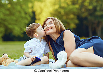 Mother with child playing on grass at sunset in summer