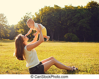 Mother with child playing on grass at sunset.