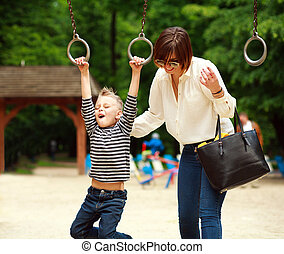 Mother with child playing on swing on summer playground in park