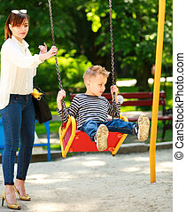 Mother with child playing on swing playground in summer park