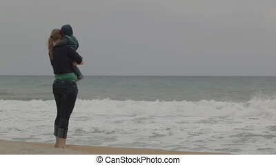 Mother with child, sea beach.