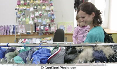 Mother with child shopping in clothing store