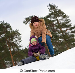mother with child sliding in the snow