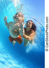Mother with child swimming underwater in the pool