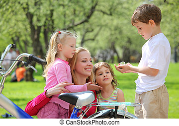 Mother with children and bicycle in park in spring