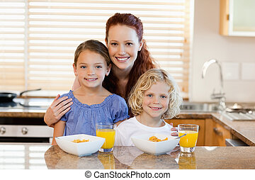 Mother with children and breakfast in the kitchen