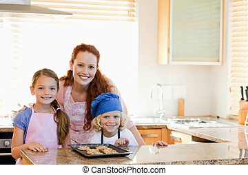 Mother with children and cookies in the kitchen
