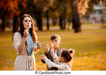 Mother with children blowing bubbles