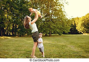 Mother with children in summer park.