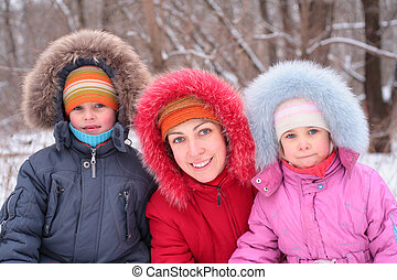 Mother with children in wood in winter