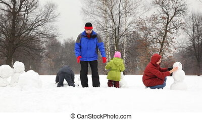 mother with children make snowman, father takes big snowball in winter, part1