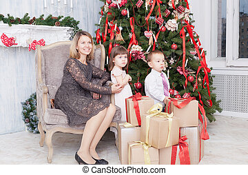 Mother with children near the Christmas fir-tree