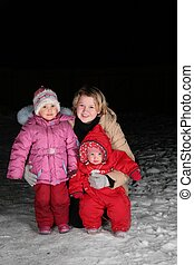 mother with children on snow in the night
