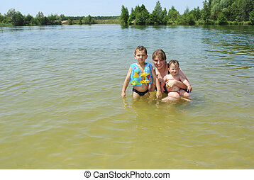 Mother with children on the lake.