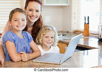 Mother with children on them laptop in the kitchen