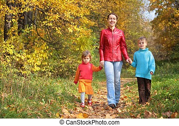 Mother with children on walk in wood
