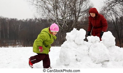 mother with children play snowballs behind fortress