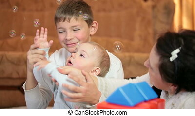 Mother with children playing on the floor of living room blowing soap bubbles